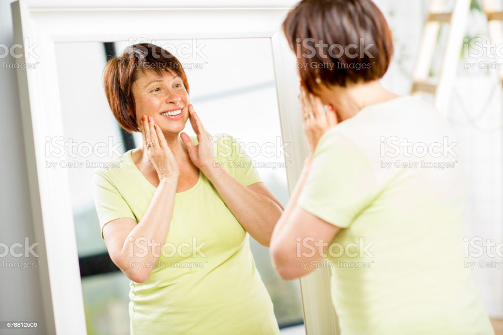 Older woman looking into the mirror photo libre de droits