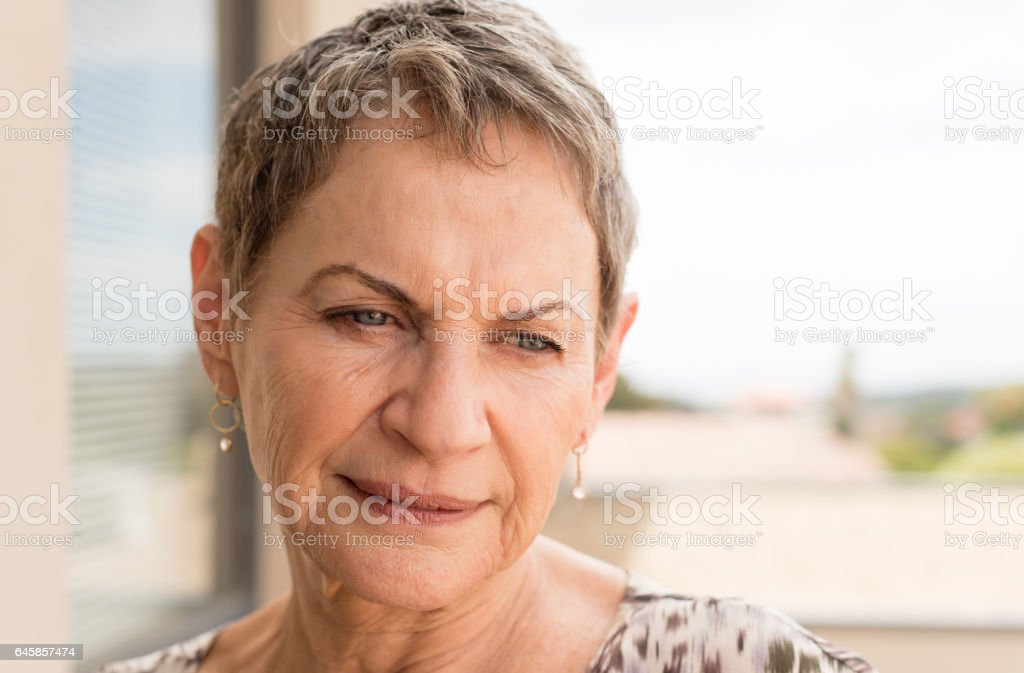 Older woman looking pensive stock photo