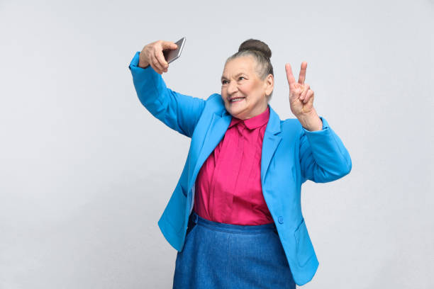 Older woman making selfie and toothy smiling aged woman making selfie with peace sing and smilling. Portrait of handsome expressive grandmother in light blue suit with collected gray hair bun hairstyle. Studio shot, isolated on gray background grandmother stock pictures, royalty-free photos & images