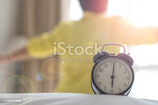 istock Older woman on bed wake up stretching in bedroom with alarm clock at 5.00 a.m. morning. Biological Clock healthcare concept 1145533960