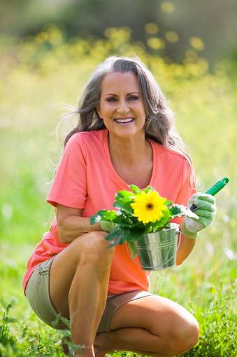 Older Woman Outdoors Holding Flower Pot Stock Photo