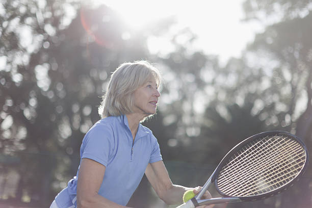 Older woman playing tennis outdoors stock photo