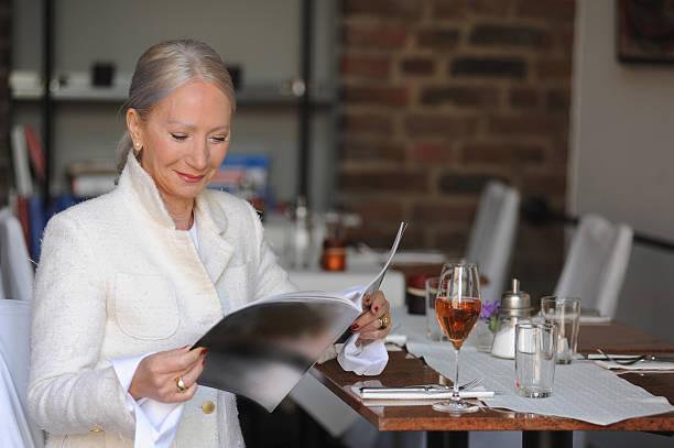 ältere frau lesen magazin im café - restaurant köln stock-fotos und bilder