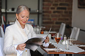 Older woman reading magazine in cafe