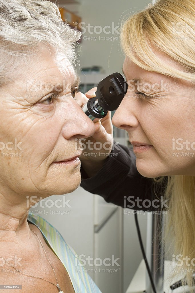 Older woman receiving eye test by female doctor royalty-free stock photo