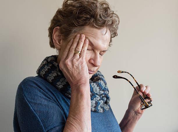 Older woman rubbing eyes stock photo