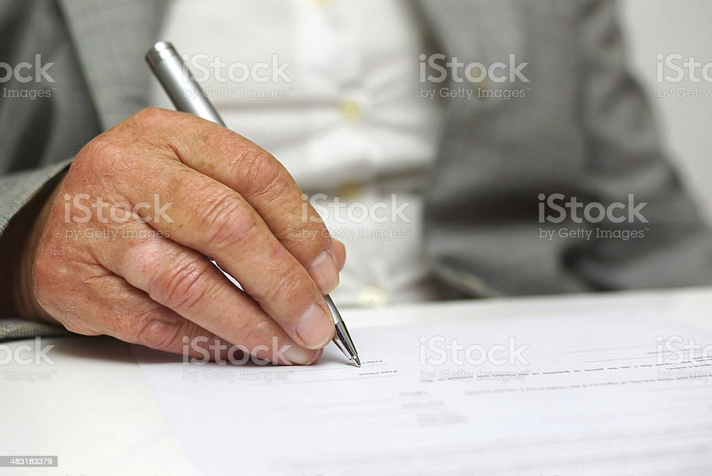 older woman signing the document stock photo