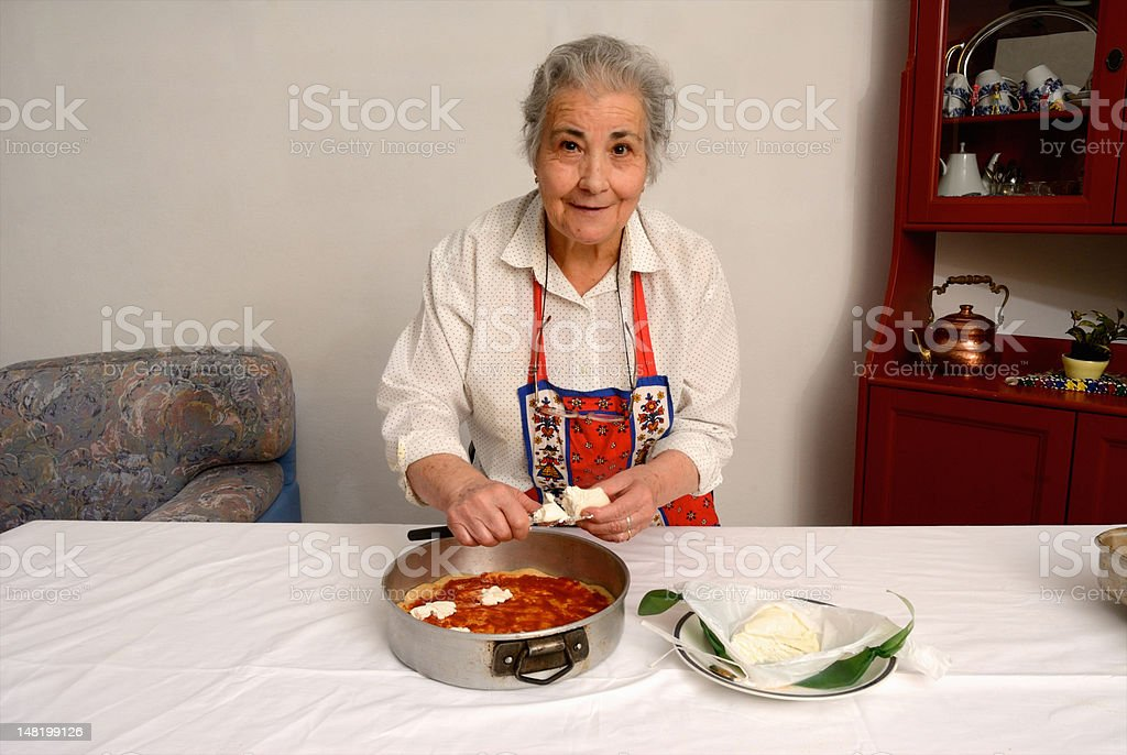 Older woman slicing cheese for pizza stock photo