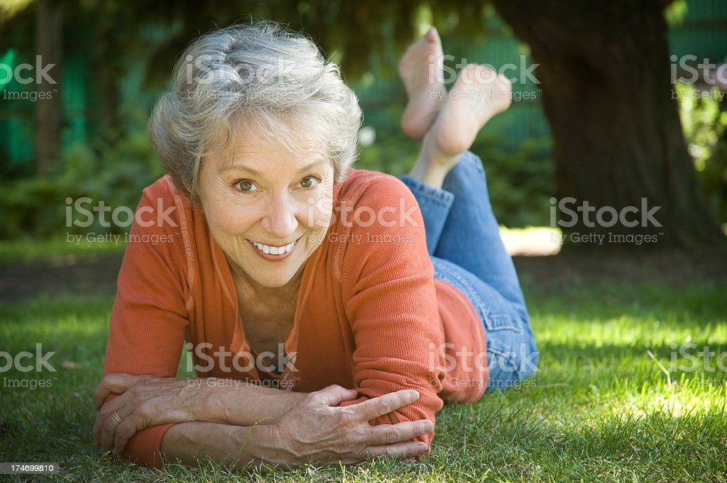 Older woman smiling and leaning on her elbows in the grass royalty-free stock photo