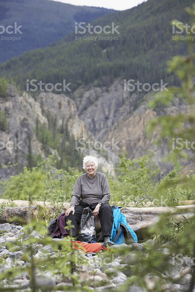 older woman smiling in mountain valley foto de stock libre de derechos