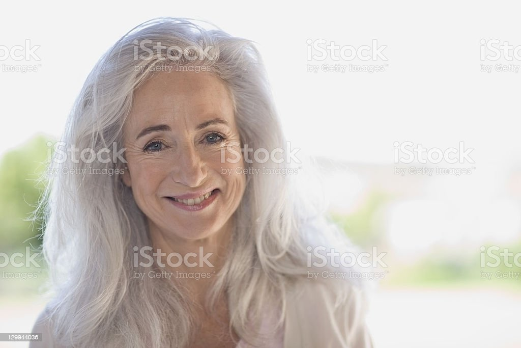 Older woman smiling outdoors stock photo