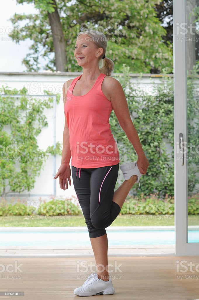 Older woman stretching at home stock photo