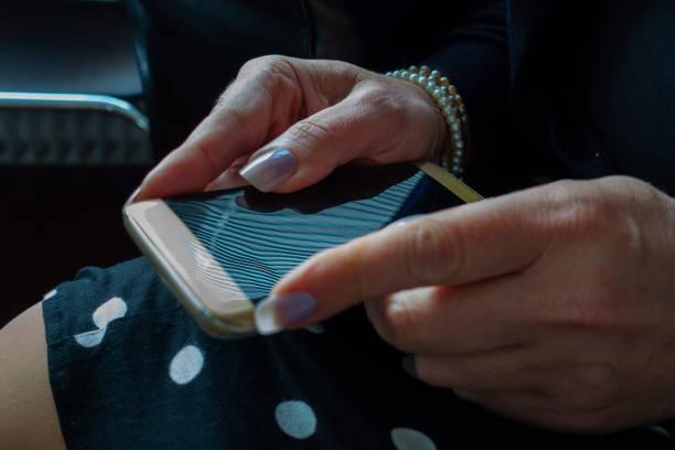 femme âgée à l'aide de son smartphone sur ses genoux - cosmetique store photos et images de collection
