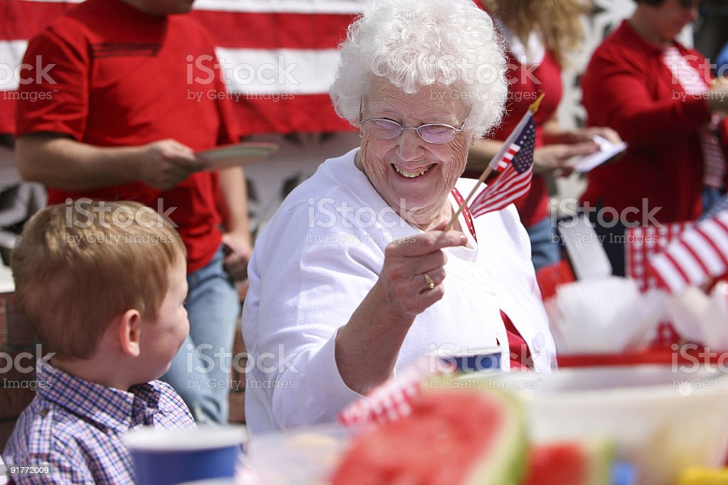 Older woman waves small American flag smiling at young boy stock photo