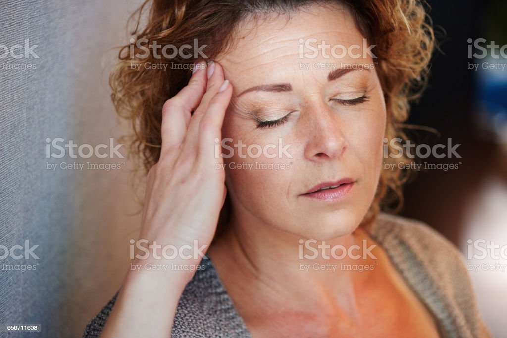 Older woman with hand to head in pain stock photo