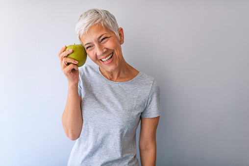 Older woman with healthy food indoors.