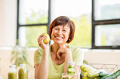 Portrait of a beautiful older woman with green healthy food on the table indoors on the window background