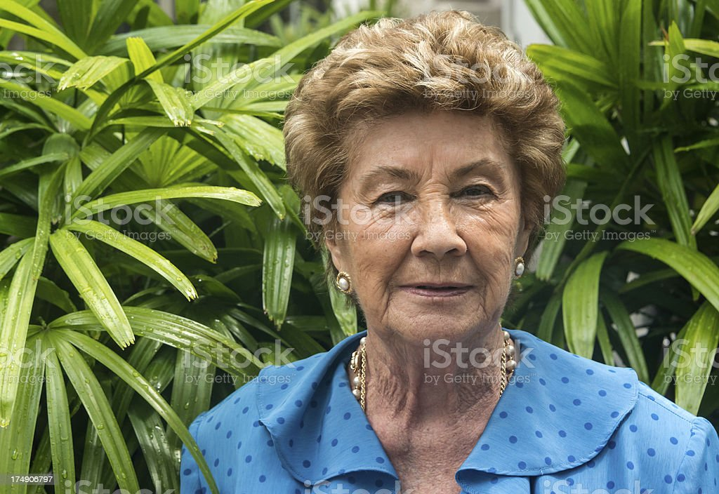 Older woman with shorter hair siting in a garden. royalty-free stock photo
