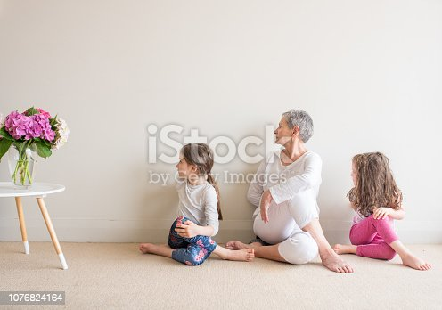 Older woman and young children in yoga seated stretch posture - grandmother and grandchildren concept (selective focus)