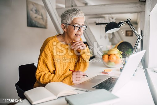 Smiling senior woman with computer at home