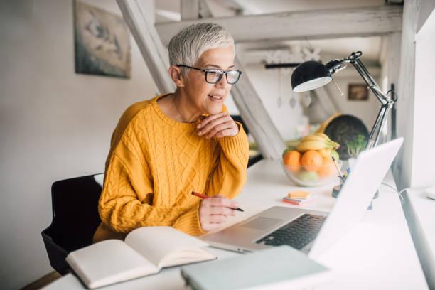 older woman working on laptop - pensionati lavoratori foto e immagini stock