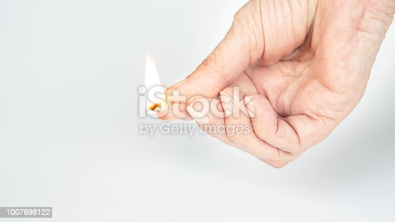 istock older womans hand holding a burning matchstick 1007698122