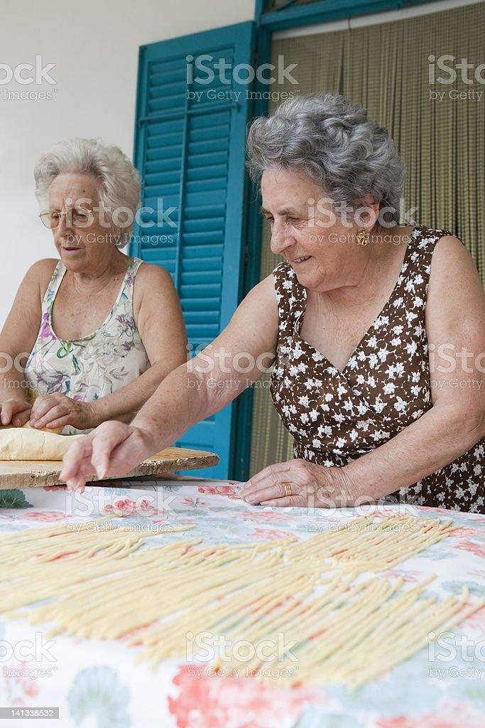 Older women making pasta together stock photo