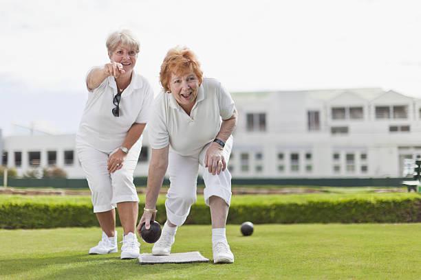 Older women playing lawn bowling stock photo