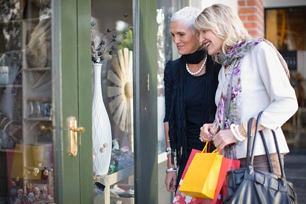 Older women window shopping together stock photo