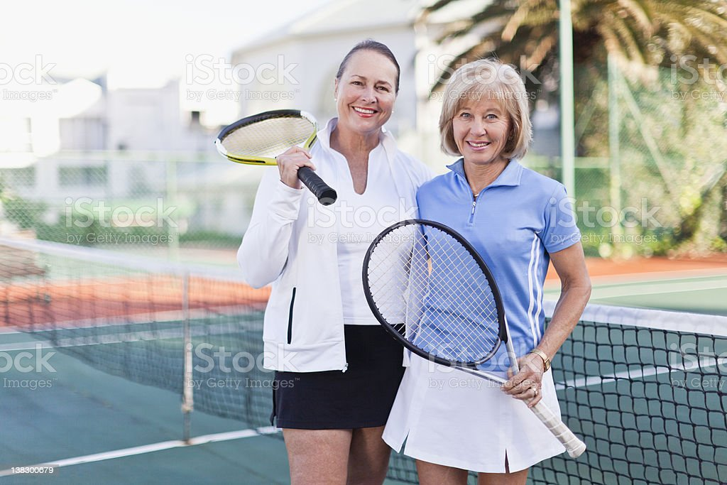 Older women with tennis rackets on court stock photo