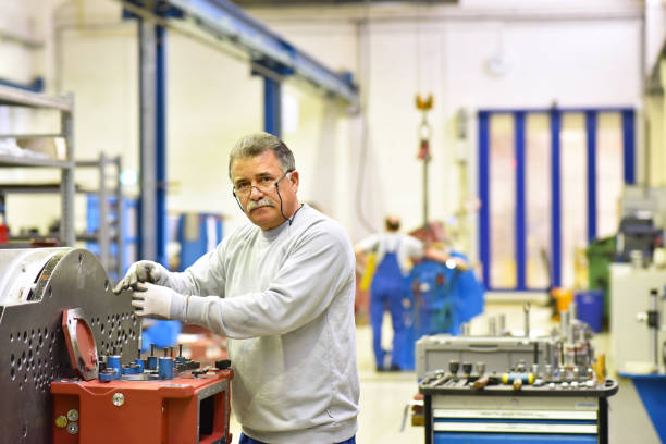 older worker in mechanical engineering - industrial factory for the production of steel gearboxes stock photo