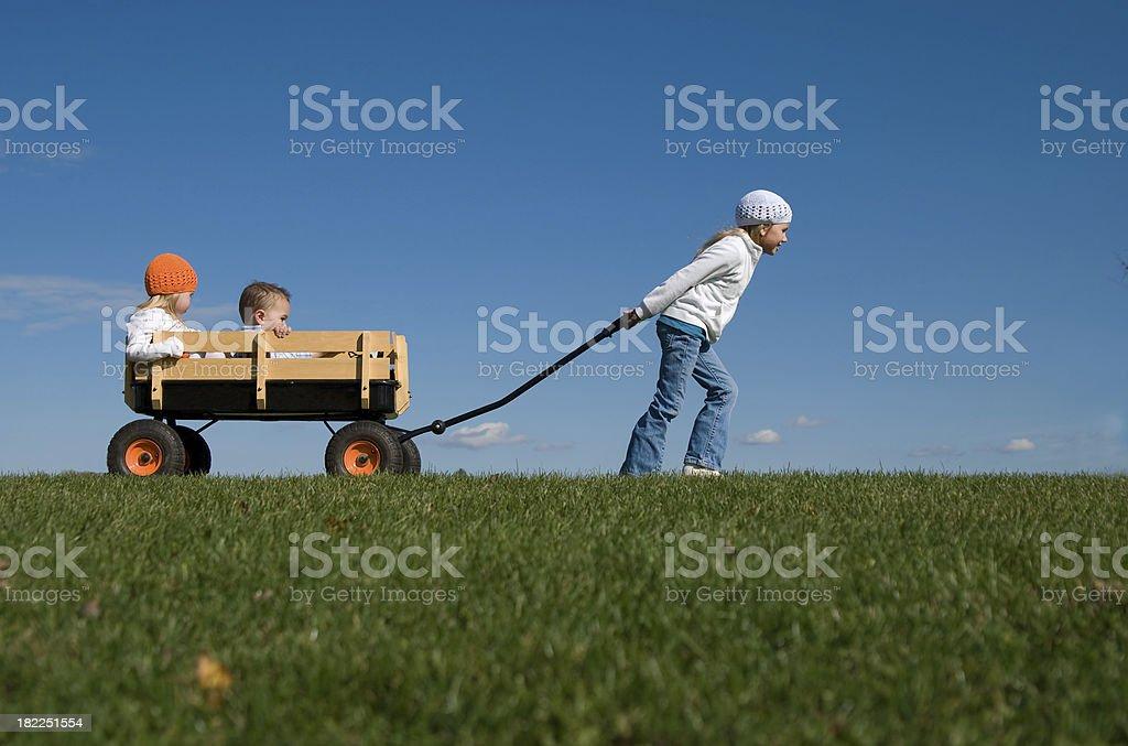 Vecchio ragazza tirando più piccolo fratelli in una carrozza - foto stock