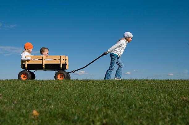 Vieille femme tirant petits frères et sœurs dans une charrette - Photo
