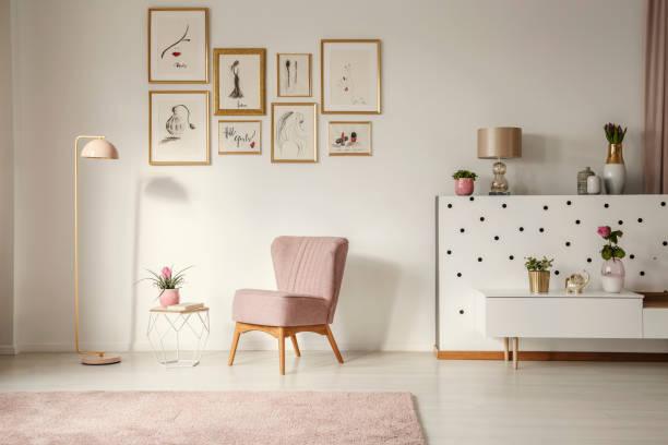 altmodische sessel, pastell rosa stehleuchte und stilvolle, goldene verzierungen in einem retro-wohnzimmer interieur mit weißen wänden - tupfen wände stock-fotos und bilder