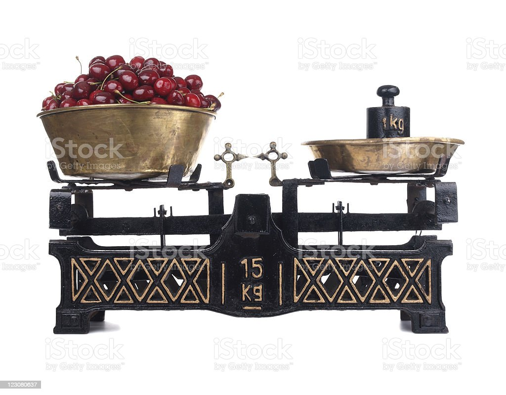 Old-fashioned balance scale with cherries isolated on white background stock photo