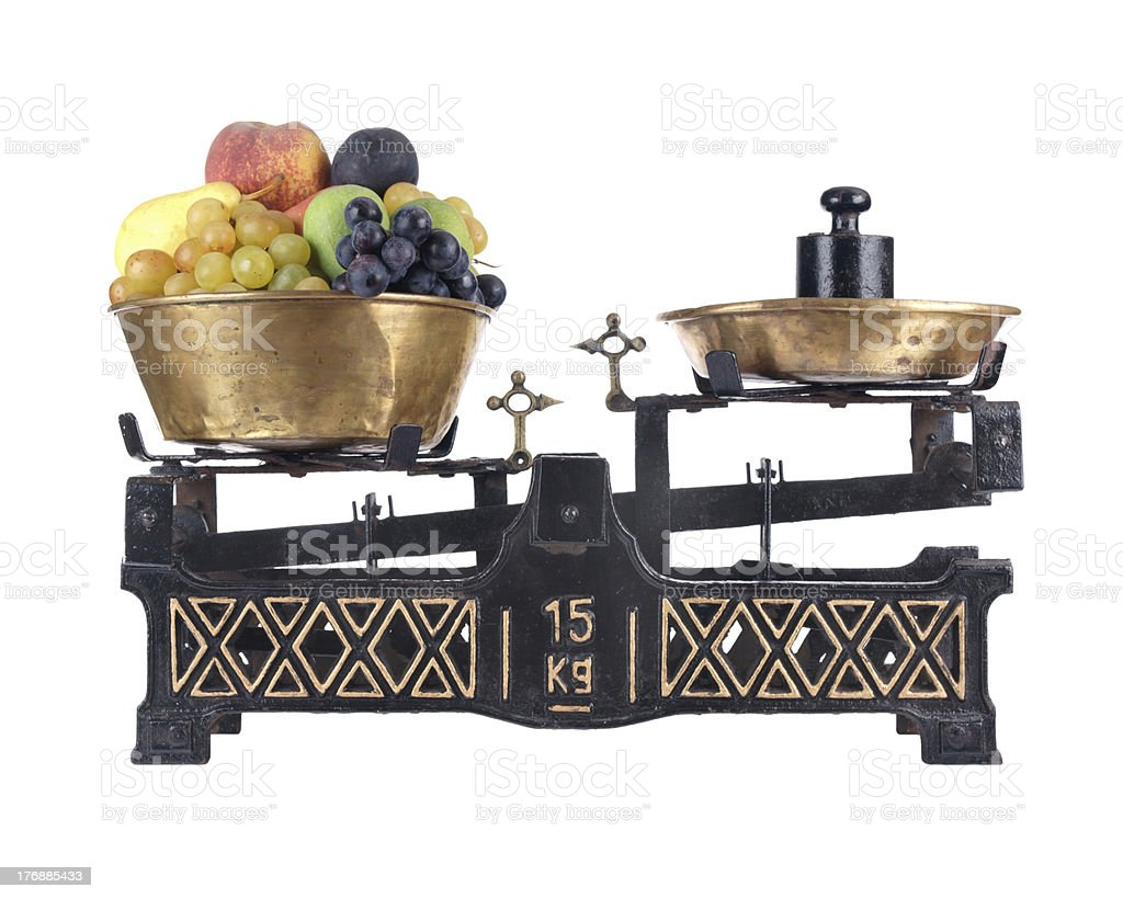 Old-fashioned balance scale with fruits, isolated on white background stock photo