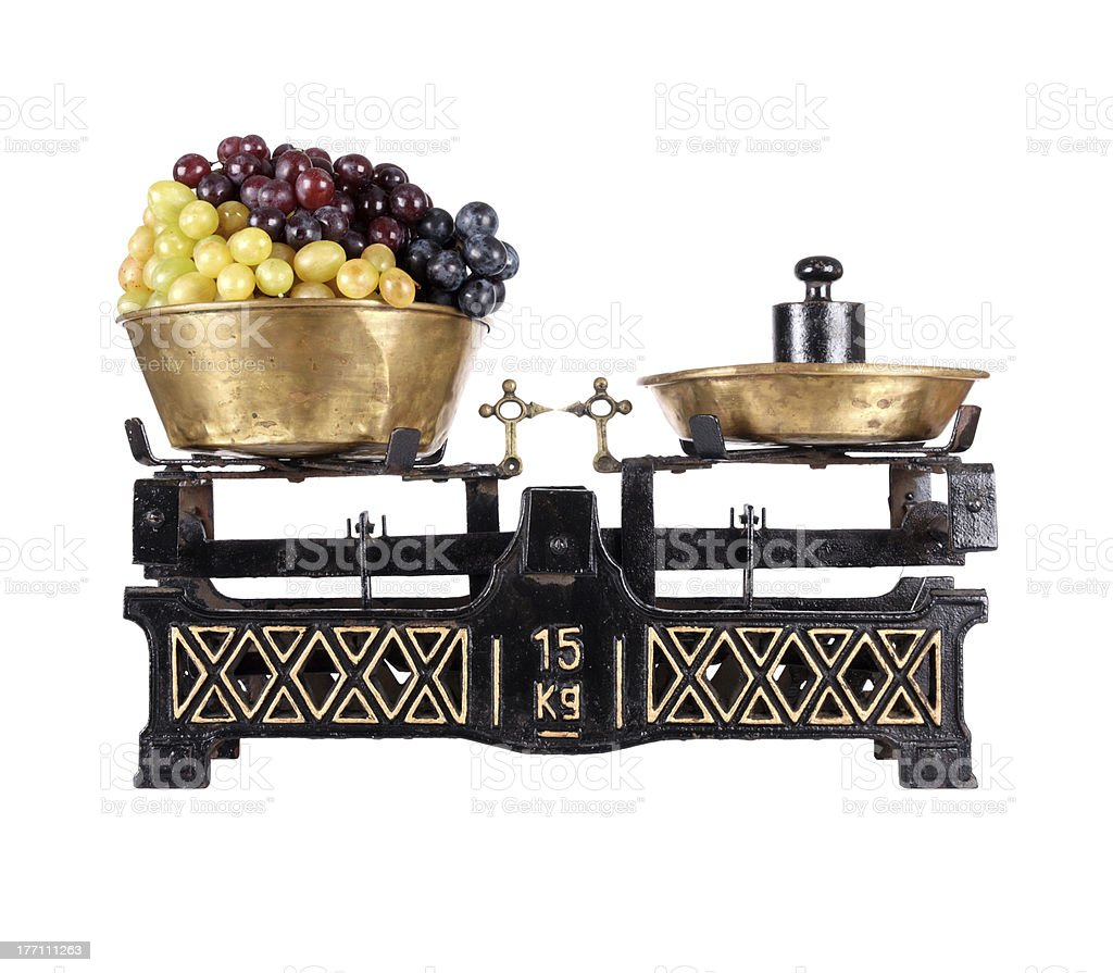 Old-fashioned balance scale with grapes isolated on white background stock photo