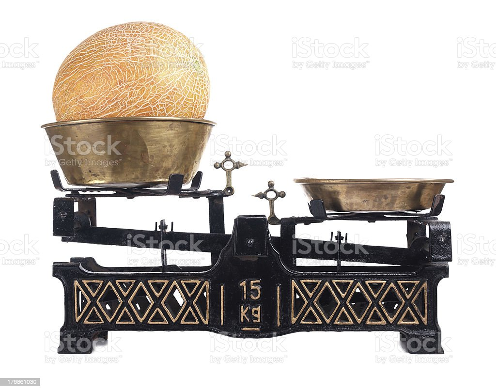 Old-fashioned balance scale with melon isolated on white background stock photo