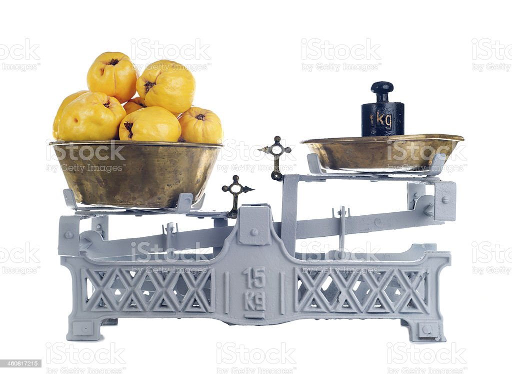Old-fashioned balance scale with quinces isolated on white background stock photo