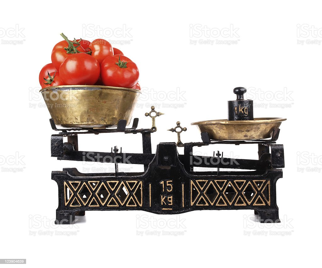 Old-fashioned balance scale with tomatoes isolated on white background stock photo