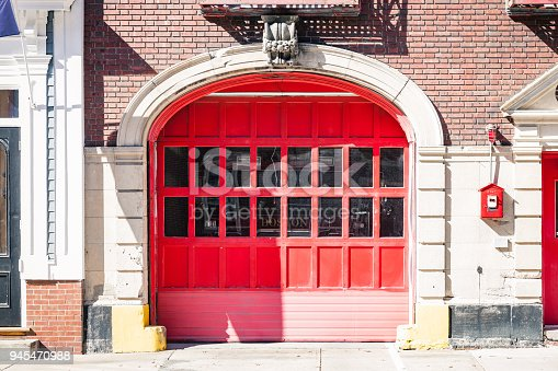 red front door in Boston. Fire truck is visible behind the glasses