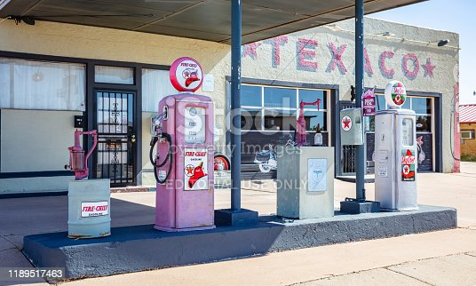 New Mexico, USA. May 14, 2019. Old-fashioned fuel pumps at gas station next to historic route 66. Building with logo background.