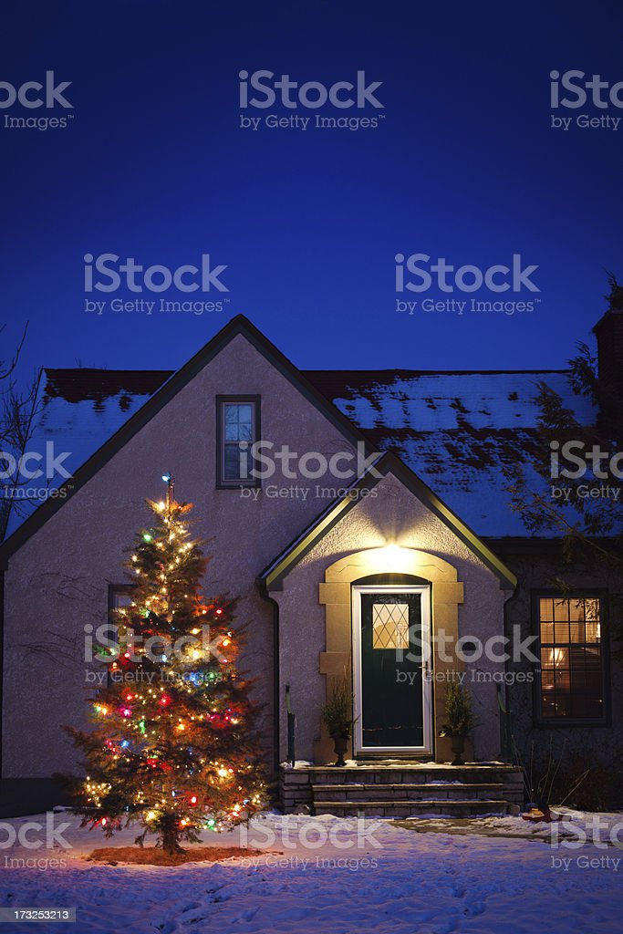 old fashioned house with decorated christmas tree lights in snowy yard royalty free stock