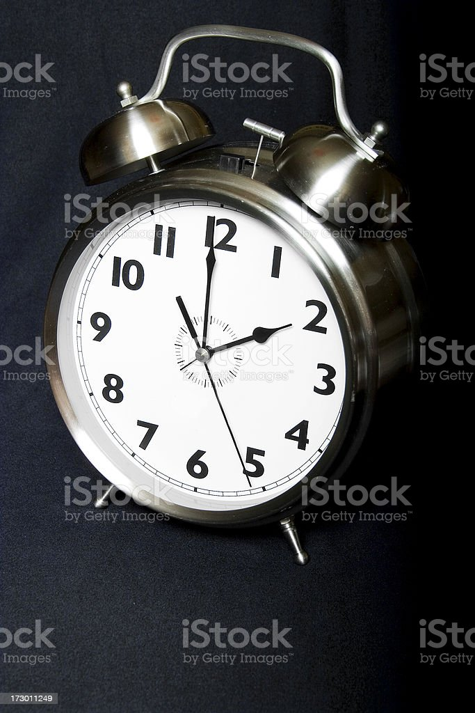 Old-fashioned iconic metal alarm clock face displays two o\'clock as...