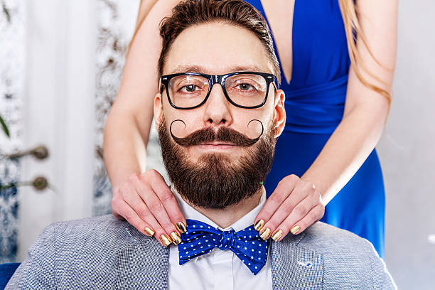 Old-fashioned man with a beard and curled mustache Woman with manicure straightens a bow tie to old-fashioned man in glasses with a beard and curled mustache. mustache stock pictures, royalty-free photos & images