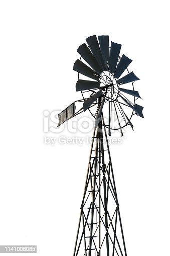 Low angle view of an old-fashioned, multi-bladed, metal wind pump atop a lattice tower in backlight, cut out on white background.