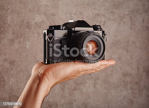 Old-fashioned professional vintage SLR analog film camera in hand