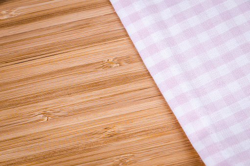 Old-fashioned pink tablecloth background with large copy space for your text. Soft post-processing. Vignette. Photo made with high quality photo equipment in a modern indoor studio.