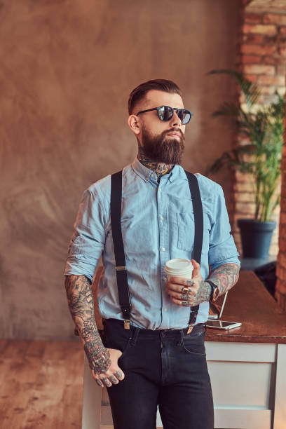 Old-fashioned tattooed hipster wearing a shirt and suspenders, in a sunglasses, standing with a cup of a coffee near a desk with a laptop, looking out the window in an office with a loft interior. Old-fashioned tattooed hipster wearing a shirt and suspenders, in a sunglasses, standing with a cup of a coffee near a desk with a laptop, looking out the window in an office with loft interior. suspenders stock pictures, royalty-free photos & images