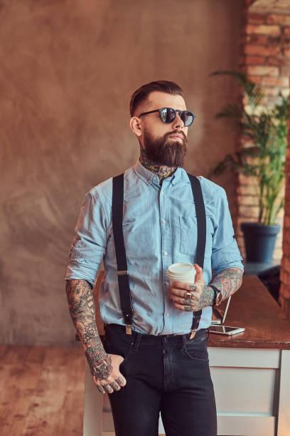 bir ofiste bir çatı katı iç pencere bakarak bir gömlek ve pantolon askısı, bir dizüstü bilgisayar ile bir danışma yakınındaki bir kahve ile ayakta bir güneş gözlüğü giyiyor eski moda dövmeli hippi. - pantolon askısı stok fotoğraflar ve resimler